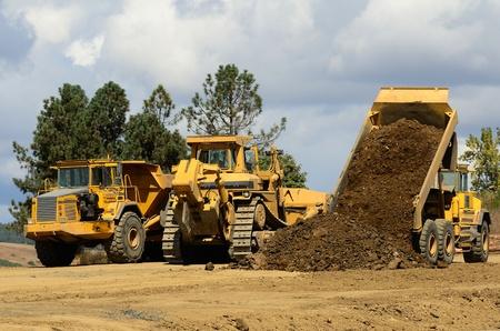 大型トラックのブルドーザーとオレゴン州で新しい道プロジェクトで大型の関節ダンプ トラック