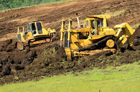 A large bulldozer grading a hillside in preperation for a major highway intersection project in Oregon Stock Photo