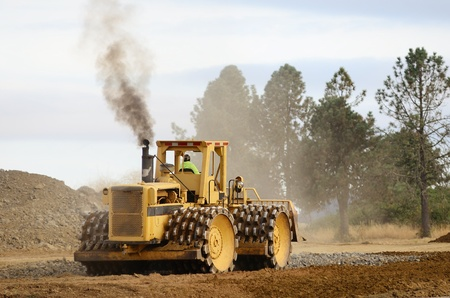 Steel wheel compactor working the grade for a new road project in Oregon Stock Photo - 10945818