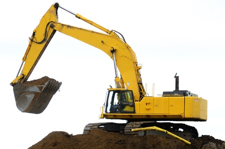 dumps: A large track hoe exchavator working on removing a dirt hill for a new road project in Oregon