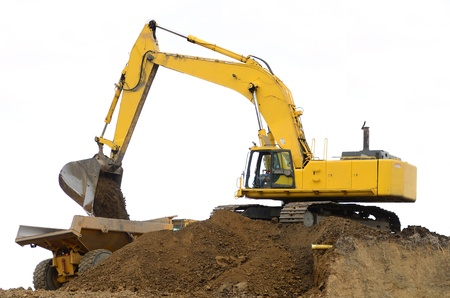 excavator: A large track hoe exchavator working on removing a dirt hill for a new road project in Oregon