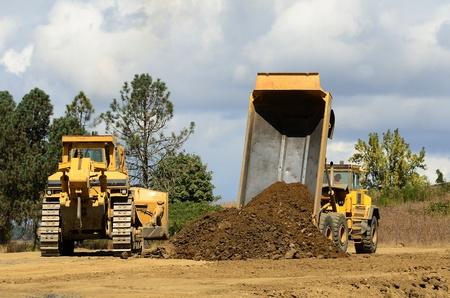 basurero: Una excavadora gran pista y un gran cami�n volcado en la articulaci�n de un nuevo proyecto vial en Oregon Foto de archivo