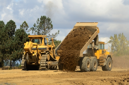 sand quarry: A large track bulldozer and a large articulating dump truck at a new road project in Oregon Stock Photo