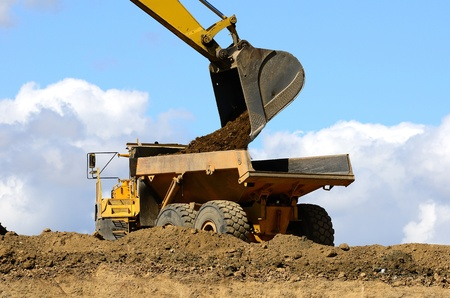 loads: A large track hoe exchavator loads a large articulating dump truck at a new road project in Oregon Stock Photo