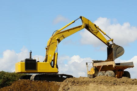 A large track hoe exchavator loads a large articulating dump truck at a new road project in Oregon Stock Photo