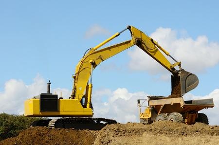 camion volquete: Una gran pista de azada exchavator cargas de un gran cami�n volcado en la articulaci�n de un nuevo proyecto vial en Oregon