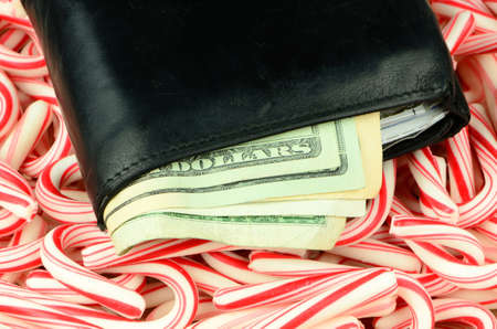 Illustrating the high cost of the Christmas holidays, a wallet full of money lies on a bed of candy canes. photo