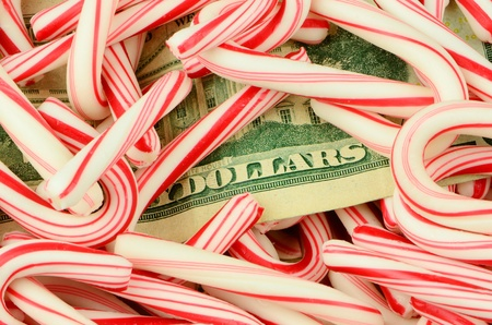 Illustrating the high cost of the Christmas holidays, money lies on a bed of candy canes. Stock Photo - 11097052