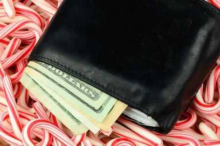 christmas debt: Illustrating the high cost of the Christmas holidays, a wallet full of money lies on a bed of candy canes. Stock Photo