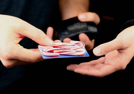 To illustrate the high cost of Christmas a candy cane credit card is passed to a store clerk. Stock Photo - 11097034