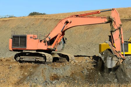 A large tracked excavator working a rock pile for a new interstate 5 interchange near Roseburg Oregon photo