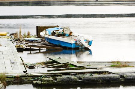 A small fishing boat on a deteriorated dock in Florence Oregon Stock Photo - 11488277