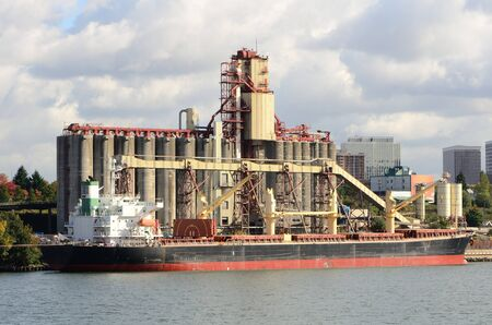 Large grain ship next to a silo facility on the Willamette River in Portland Oregon