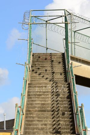 razorwire: Large set of concrete stairs on a railroad pedastrian overpass