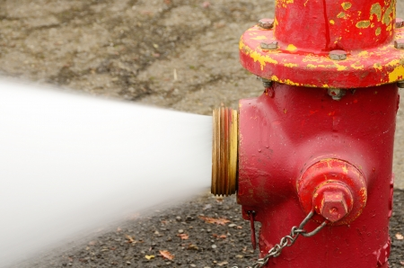 Open 5 inch butt of an industrial fire hydrant being sprayed into a log pod in Creswel Oregon Stock Photo