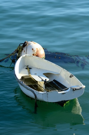 hooked up: Small harbor boat hooked up to a large bouy in San Luis Obisbo Bay, CA
