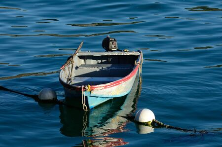 luis: Small harbor boat hooked up to a large bouy in San Luis Obisbo Bay, CA