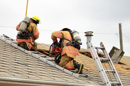 Roseburg, OR USA - July 21, 2011: Roseburg Fire Fighters participating in a vertical ventilation drill at a old hotel.