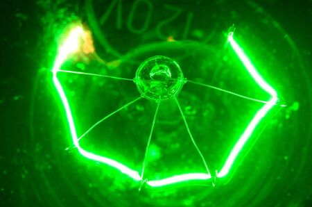 Lightbulb experiment showing heated filament in green bulb