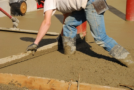 Workers pouring a concrete pad outside a new commercial building. photo
