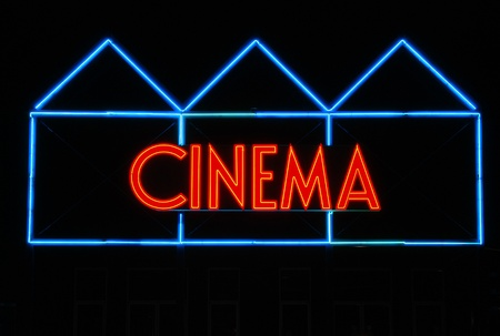 Neon Cinema sign outside a movie theater Stock Photo