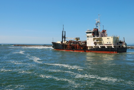 coquille: Large boat at the entrance of Coquille RiverJetty near Bandon Oregon checking channel depth Editorial
