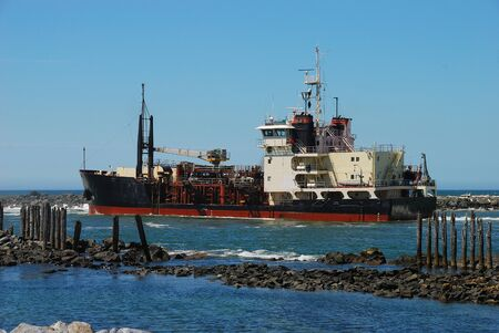 Large boat at the entrance of Coquille RiverJetty near Bandon Oregon checking channel depth Stock Photo - 12299136