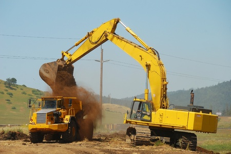 Large exchavator loading a large dump truck at a new freeway interchange project near Roseburg Oregon