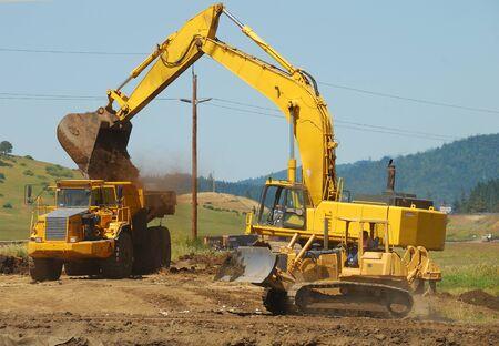 Large exchavator loading a large dump truck at a new freeway interchange project near Roseburg Oregon