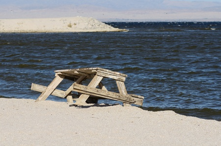 overtaken: Old picnic table being overtaken by surf in the Salton Sea in California