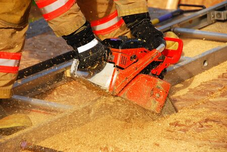 Vertical ventilation drill behind fire station using vent saw  Stock Photo - 12674008