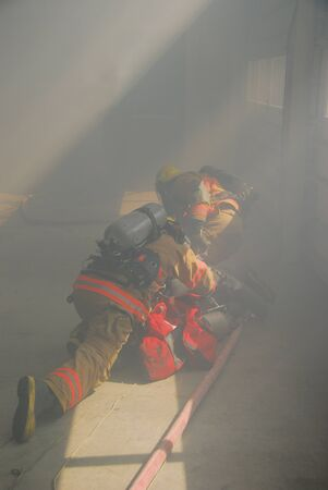 fire fighters crawling through a smoky structure with fire hose and scba Redactioneel