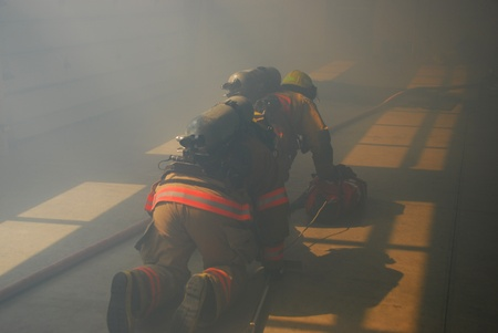 fire fighters crawling through a smoky structure with fire hose and scba