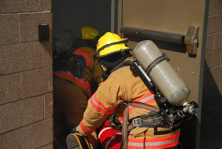 turnouts: fire fighters crawling through a smoky structure with fire hose and scba Editorial
