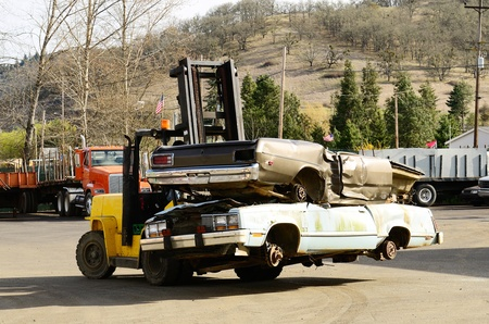 junk: A large lift truck moving discarded autos for metal recyling