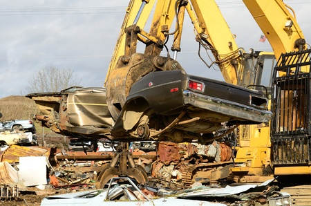A large excavator crushing and piling discarded autos for metal recyling