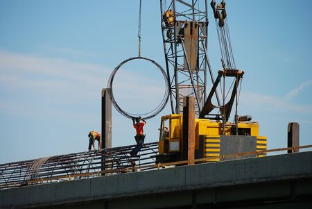 Iron workers moving rebar rings using a large crane into place for a new support pier on the Southbound portion of the Interstate 5 Shady Bridge project Stock Photo - 13731294