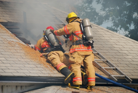 response: Fire fighters enlarging the vent hole on a single family dwelling on fire Stock Photo