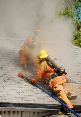 Fire fighters enlarging the vent hole on a Single family dwelling on fire