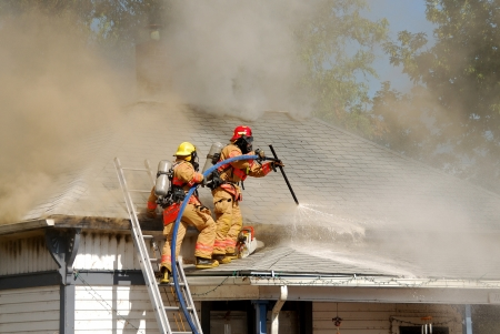 response: fire fighter performing horizontal ventilation on a single family house Stock Photo