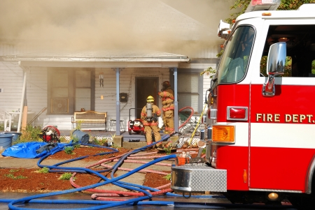 camion pompier: Pompiers d'attaque et de sauvegarde lignes en face d'une habitation unifamiliale sur le feu Banque d'images