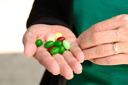 Jellybeans and sour candies in a hand Stock Photo - 13749112