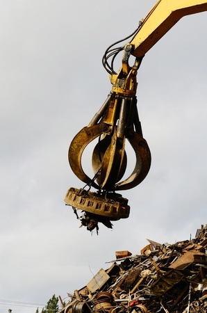 salvage yard: Large tracked excavator working a steel pile at a metal recycle yard with a magnet.
