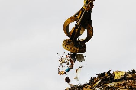 Excavadora seguido trabajando un montón de acero en un patio de reciclaje de metal con un imán.