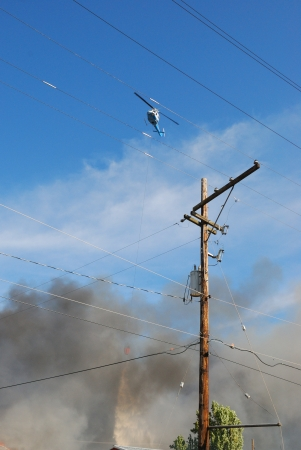 Helicopter Droping Water on the Fire, Natural cover fire that extended into a structure brought out