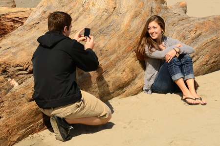 A young couple spending time on the Oregon Coast using a camera to make memories photo