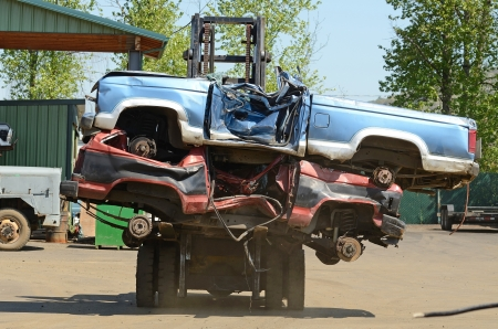 Large lift truck moving crushed cars at a metal recycle yard Stock Photo