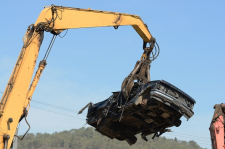 Large excavator with a claw crushing and piling old cars at a metal recycle plant photo