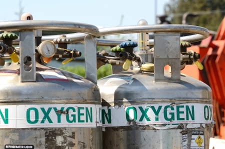 Two large liquid oxygen tanks at the ready in a metal recycling yard