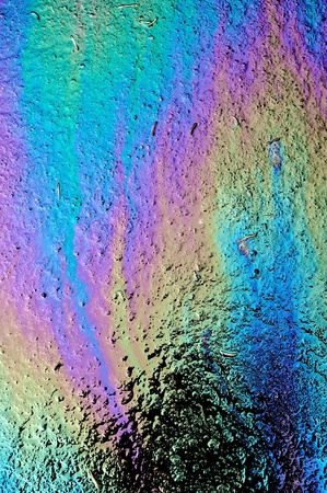 colorful water surface: Gasoline that had leaked onto a wet parking lot creates a rainbow oil slick